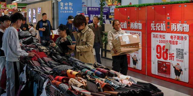 A worker carrying boxes of goods walks by women selecting handbags at a commercial building in Beijing, Friday, Oct. 18, 2019. (AP Photo/Andy Wong)