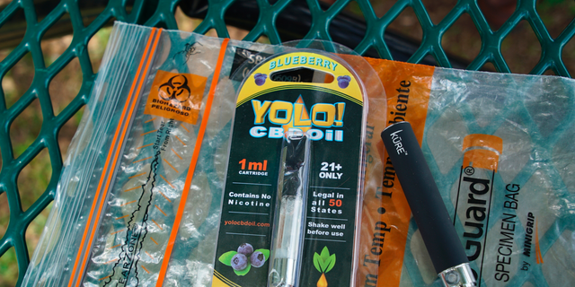 In this May 8, 2019, file photo, a Yolo! brand CBD oil vape cartridge sits alongside a vape pen on a biohazard bag on a table at a park in Ninety Six, S.C. (AP Photo/Allen G. Breed, File)