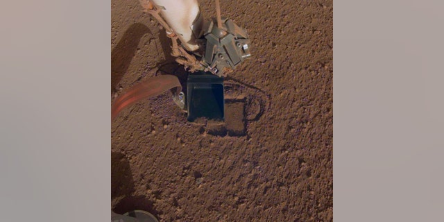 This October 2019 photo made available by NASA shows InSight's heat probe digging into the surface of Mars. On Thursday, Oct. 17, 2019, NASA says the drilling device has penetrated three-quarters of an inch (2 centimeters) over the past week, after hitting a snag seven months ago. While just a baby step, scientists are thrilled with the progress. (NASA/JPL-Caltech via AP)