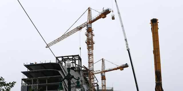 Workers in a bucket begin the process of planting explosive charges on two unstable cranes at the Hard Rock Hotel, which underwent a partial, major collapse Saturday, Oct. 12, in New Orleans, viewed Thursday, Oct. 17, 2019. Authorities say explosives will be strategically placed on the two unstable construction cranes in hopes of bringing them down with a series of small controlled blasts ahead of approaching tropical weather. Officials hope to bring the towers down Friday without damaging nearby businesses and historic buildings in and around the nearby French Quarter. (AP Photo/Gerald Herbert)