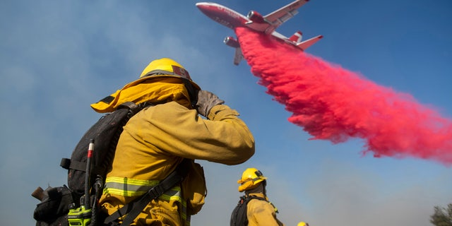 Firefighters brace themselves for incoming fire retardant during the Easy Fire, Wednesday, Oct. 30, 2019, in Simi Valley, Calif.