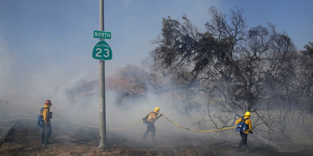 Firefighters put out hot spots along Highway 23, closed to traffic due to the Easy Fire, Wednesday, Oct. 30, 2019, in Simi Valley, Calif.