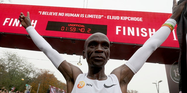 Marathon runner Eliud Kipchoge from Kenya celebrates under the clock after crossing the finish line of the INEOS 1:59 Challenge after 1:59:40 in Vienna, Austria, Saturday, Oct. 12, 2019. He is the first human ever to run a marathon under two hours. (AP Photo/Ronald Zak)