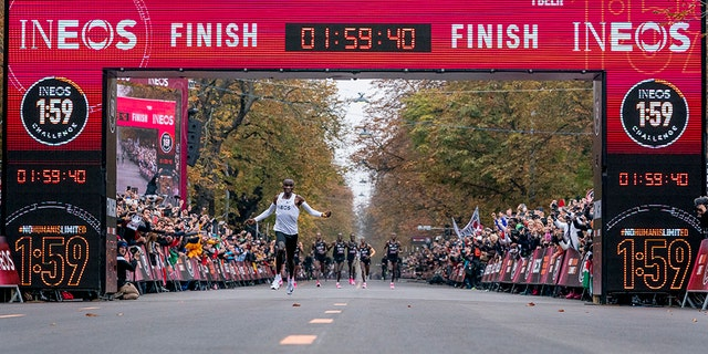 In this photo made available by The INEOS 1:59 Challenge on Saturday, Oct. 12, 2019, Eliud Kipchoge celebrates as he crosses finish line and makes history to become the first human being to run a marathon in under 2 hours. (Bob Martin/The INEOS 1:59 Challenge via AP)