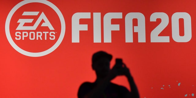 """A visitor takes a picture at the booth of the """"FIFA 20"""" football game at the Gamescom video games trade fair in Cologne, western Germany, on August 20, 2019 - file photo."""