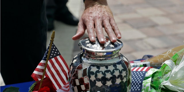 Mourners reach out an touch an urn holding the remains U.S. Army veteran Edward K. Pearson during an open funeral service Tuesday, Oct. 1, 2019, at the Sarasota National Cemetary in Sarasota, Fla.