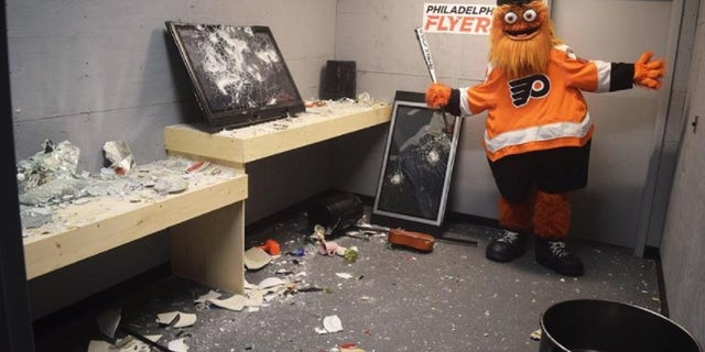 """Philadelphia Flyers mascot Gritty poses after a session in the """"Rage Room."""""""