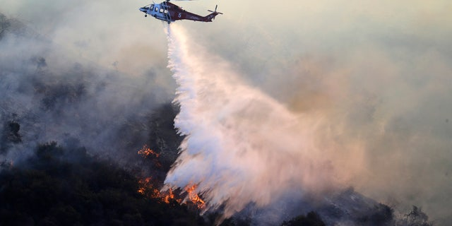 A helicopter drops water as the Getty fire burns on Mandeville Canyon Monday, Oct. 28, 2019, in Los Angeles.