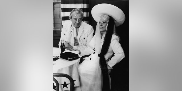 "American actors John Huston and Mae West sit at a restaurant table in a still from the film ""Myra Breckinridge"" directed by Michael Sarne, 1970."