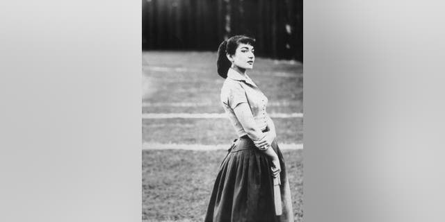 Portrait of Greek-American opera singer Maria Callas (1923 - 1977), standing outdoors in a field and holding a hand fan, Rome, Italy.