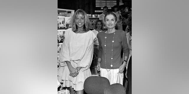 Good friends Carly Simon and Jackie Onassis pose for a picture at Bunch of Grapes Bookstore on Martha's Vineyard, Mass., on Sept. 2, 1989.