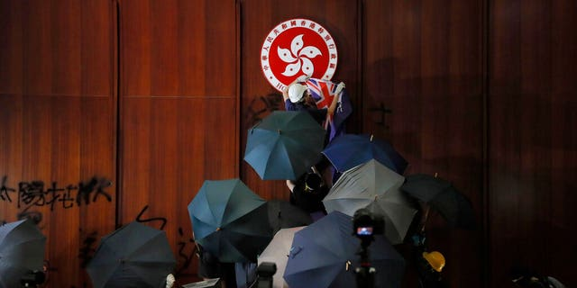 FILE - In this July 1, 2019, file photo, a protester covers the Hong Kong emblem with a Hong Kong colonial flag after they broke into the Legislative Council building in Hong Kong. Hong Kong authorities on Wednesday, Oct. 23, 2019 withdrew an unpopular extradition bill that sparked months of chaotic protests that have since morphed into a campaign for greater democratic change. (AP Photo/Kin Cheung, File)