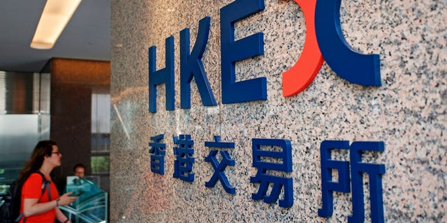 A woman walks past a logo of the Hong Kong Stock Exchanges in Hong Kong, Tuesday, Oct. 8, 2019. (AP Photo/Kin Cheung)