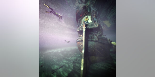 Divers swim over a digital reconstruction of the ship during a virtual dive.