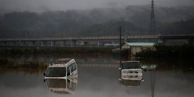 Two vehicles are submerged in floodwaters Monday, Oct. 14, 2019, in Hoyasu, Japan.