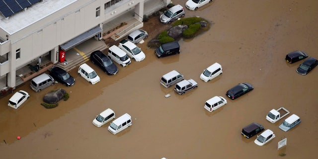 Vehicles are seen under water following the typhoon-hit town of Marumori, Miyagi prefecture, Japan , Monday, Oct. 14, 2019.
