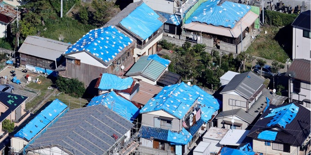 This Oct. 9, 2019, photo shows the sheet-covered roofs of the houses damaged by typhoon Faxai in Kyonan, near Tokyo. Japan's weather agency is warning a powerful typhoon may bring torrential rains to central Japan over the weekend.