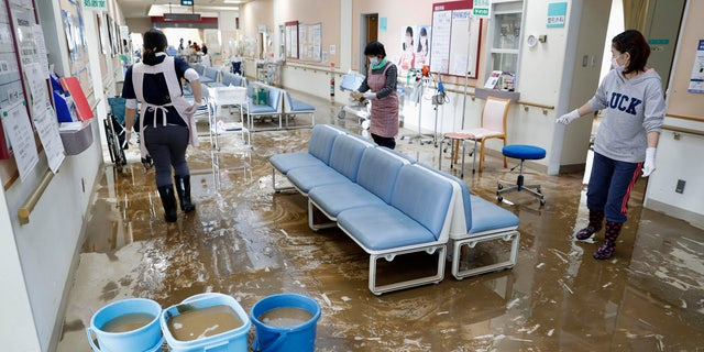 Staff members clean a hospital damaged by Typhoon Hagibis, in Marumori town, Miyagi prefecture, Japan Tuesday, Oct. 15, 2019.