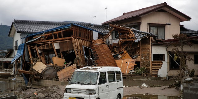 A vehicle sits in front of a home destroyed by Typhoon Hagibis Tuesday, Oct. 15, 2019, in Nagano, Japan.