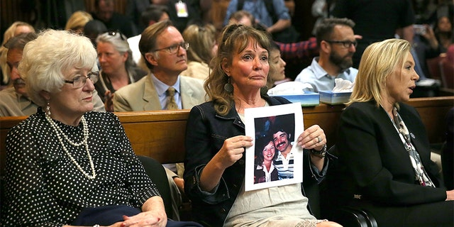An attendee holds a photo of Cheri Domingo and her boyfriend Gregory Sanchez, who were killed in 1981, during DeAngelo's arraignment.
