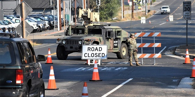 A member of Cal Guard blocks traffic from entering the town of Healdsburg on Monday following an evacuation order.