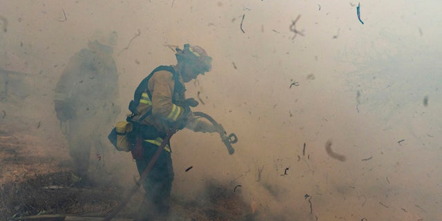 Firefighters from San Matteo work to extinguish flames from the Kincade Fire in Sonoma County, Calif., on Sunday, Oct. 27, 2019.
