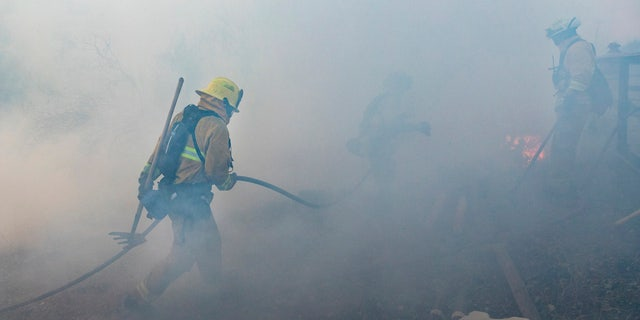 A firefighter from San Matteo pulls a hose line as crews work to suppress the Kincade Fire in Sonoma County, Calif., on Sunday, Oct. 27, 2019.