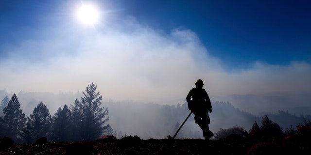 Firefighter Josh Petrell monitors the Kincade Fire burning near Healdsburg, Calif., on Tuesday, Oct. 29, 2019. AP Photo/Noah Berger
