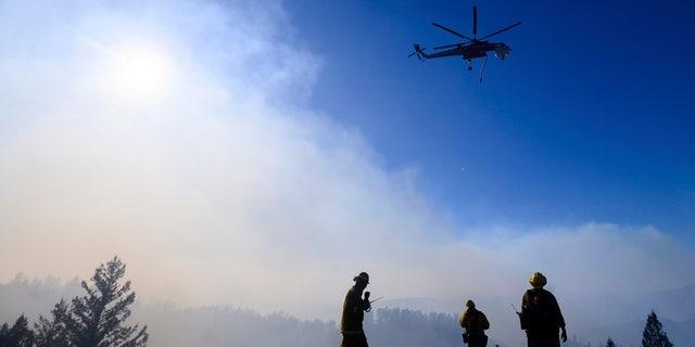 Firefighters monitor the Kincade Fire burning near Healdsburg, Calif., on Tuesday, Oct. 29, 2019.