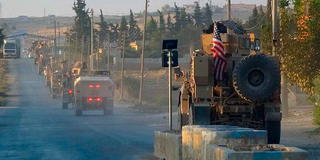 In this image provided by Hawar News Agency, ANHA, U.S. military vehicles travel down a main road in northeast Syria on Monday. (ANHA via AP)