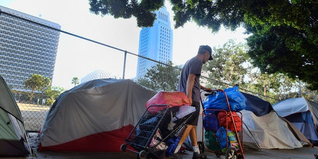 A homeless man moves his belongings from a street behind Los Angeles City Hall as crews prepared to clean the area on July 1, 2019.