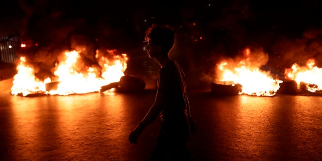 A Lebanese demonstrator walks past burning tires during the tax protest in a Beirut suburb. (Anwar Amro/AFP via Getty Images)
