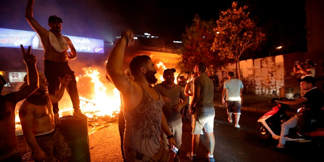 Lebanese demonstrators chant slogans as a fire burns during a protest against recent tax calls on Thursday in Beirut. (Anwar Amro/AFP via Getty Images)