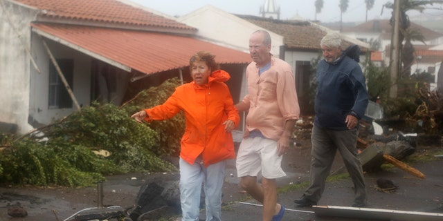 Don Marks, from Massachusetts in the US, center, and his wife Celeste walk among debris on their way to look at their wrecked seafront house in the village of Feteira, outside Horta, in the Portuguese island of Faial, Wednesday, Oct. 2, 2019.