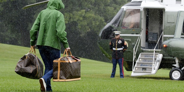 A White House aide carries Louis Vuitton bags to a helicopter prior to President Trump and first lady Melania Trump's departure from the White House on Sept. 2, 2017.