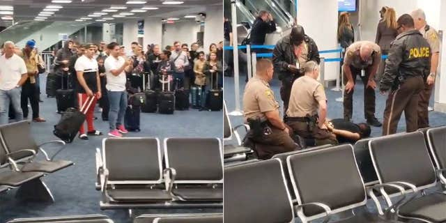 Passengers at the Miami International Airport look on after the man was removed from the plane and detained by police on Monday morning.