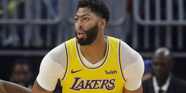 Los Angeles Lakers forward Anthony Davis dribbles during the first half of the team's preseason NBA basketball game against the Golden State Warriors in San Francisco, Saturday, Oct. 5, 2019. (AP Photo/Jeff Chiu)