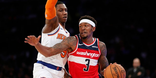 Washington Wizards guard Bradley Beal (3) drives around New York Knicks forward RJ Barrett during the first half of a preseason NBA basketball game in New York, Friday, Oct. 11, 2019. (AP Photo/Kathy Willens)