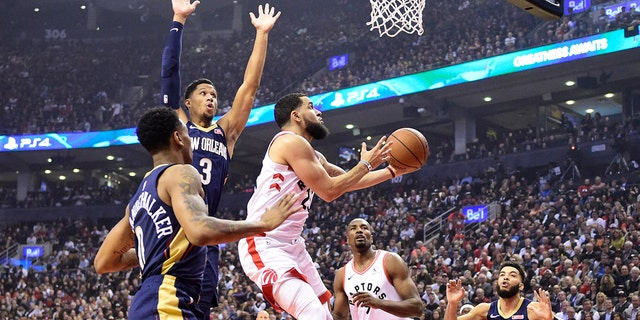 Toronto Raptors guard Fred VanVleet (23) goes to the basket as New Orleans Pelicans' Josh Hart (3) and Nickeil Alexander-Walker (0) defend during the first half of an NBA basketball game Tuesday, Oct. 22, 2019, in Toronto. (Frank Gunn/The Canadian Press via AP)