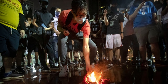 Demonstrators set a Lebron James jersey on fire during a rally at the Southorn Playground in Hong Kong, Tuesday, Oct. 15, 2019.  (AP Photo/Mark Schiefelbein)