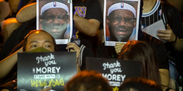 Demonstrators hold up photos of LeBron James grimacing during a rally at the Southorn Playground in Hong Kong, Tuesday, Oct. 15, 2019. (AP Photo/Mark Schiefelbein)
