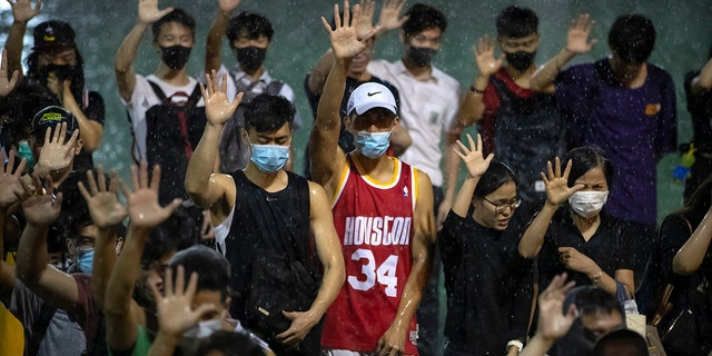 A demonstrator wearing Houston Rockets jersey holds up his hand with fellow demonstrators during a rally at the Southorn Playground in Hong Kong, Tuesday, Oct. 15, 2019. (AP Photo/Mark Schiefelbein)