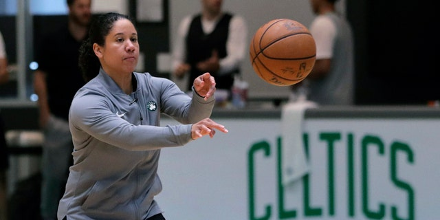 """FILE - In this July 1, 2019, file photo, Boston Celtics assistant coach Kara Lawson passes the ball at the team's training facility in Boston. Celtics guard Gordon Hayward said Lawson has already made her presence felt. """"She's been good as far as just the experience she has as a basketball player,"""" Hayward said. """"Reading the game and kind of little things she sees coaching on the sideline. Having somebody that well-versed in basketball, that experience is good."""" (AP Photo/Charles Krupa, File)"""