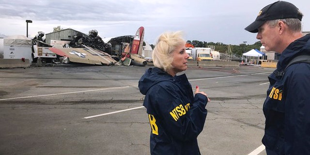 In this photo released via Twitter by the National Transportation Safety Board, NTSB board Member Jennifer Homendy, left, and investigator Dan Bower stand at the scene where a World War II-era bomber plane, left, crashed at Bradley International Airport in Windsor Locks, Conn., Wednesday, Oct. 2, 2019.