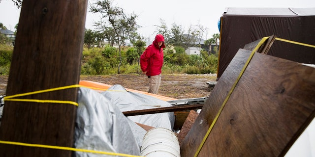 Chris Anderson ties down building materials and other objects from his lawn as Tropical Storm Nestor approached Mexico Beach, Fla..