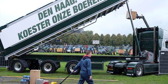 "A worker walks past a truck with a banner saying: ""The Hague: Cherish our farmers!"", refrying to the government, as tractors driven by protesting farmers line up in the background during a protest in The Hague, Netherlands, Tuesday, Oct. 1, 2019. (AP Photo/Mike Corder)"