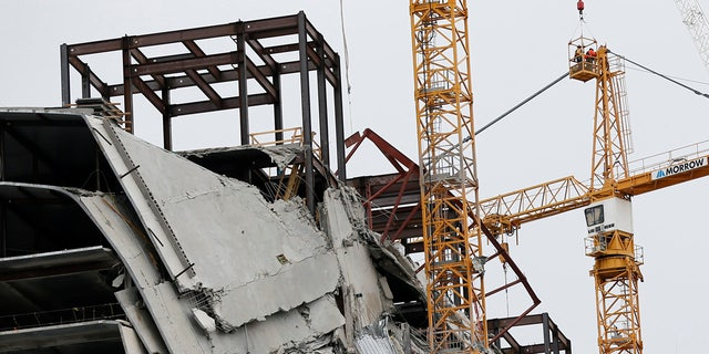 Workers preparing the two unstable cranes for implosion at the collapse site of the Hard Rock Hotel, which underwent a partial, major collapse while under construction on Oct., 12, in New Orleans.