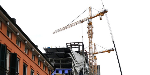 Workers in a bucket hoisted by a crane preparing the two unstable cranes for implosion at the collapse site of the Hard Rock Hotel n New Orleans on Friday.
