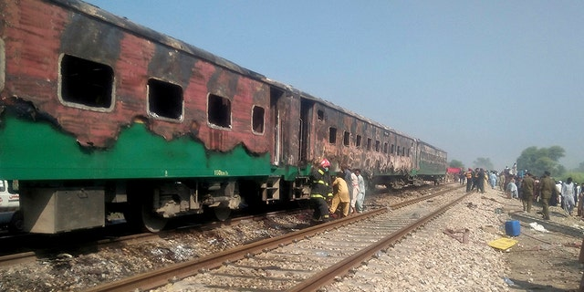 Pakistani officials examine a train damaged by a fire in Liaquatpur, Pakistan, Thursday, Oct. 31, 2019. A massive fire engulfed three carriages of the train traveling in the country's eastern Punjab province (Associated Press)