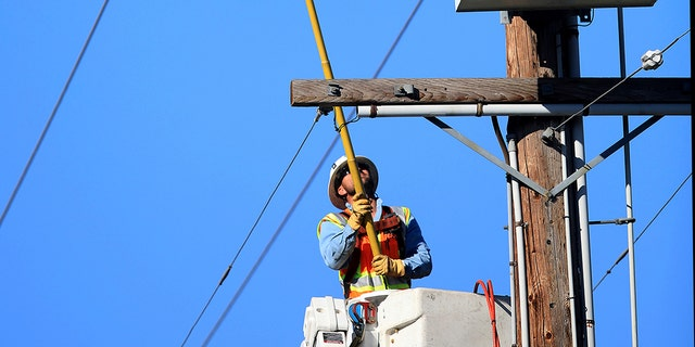 A Pacific Gas and Electric Co. crew trips a segment of power lines in Santa Rosa, Calif., Wednesday, Oct. 23, 2019, that will make it easier to restore power. The power was shut off due to the high fire danger. (Kent Porter/The Press Democrat via AP)